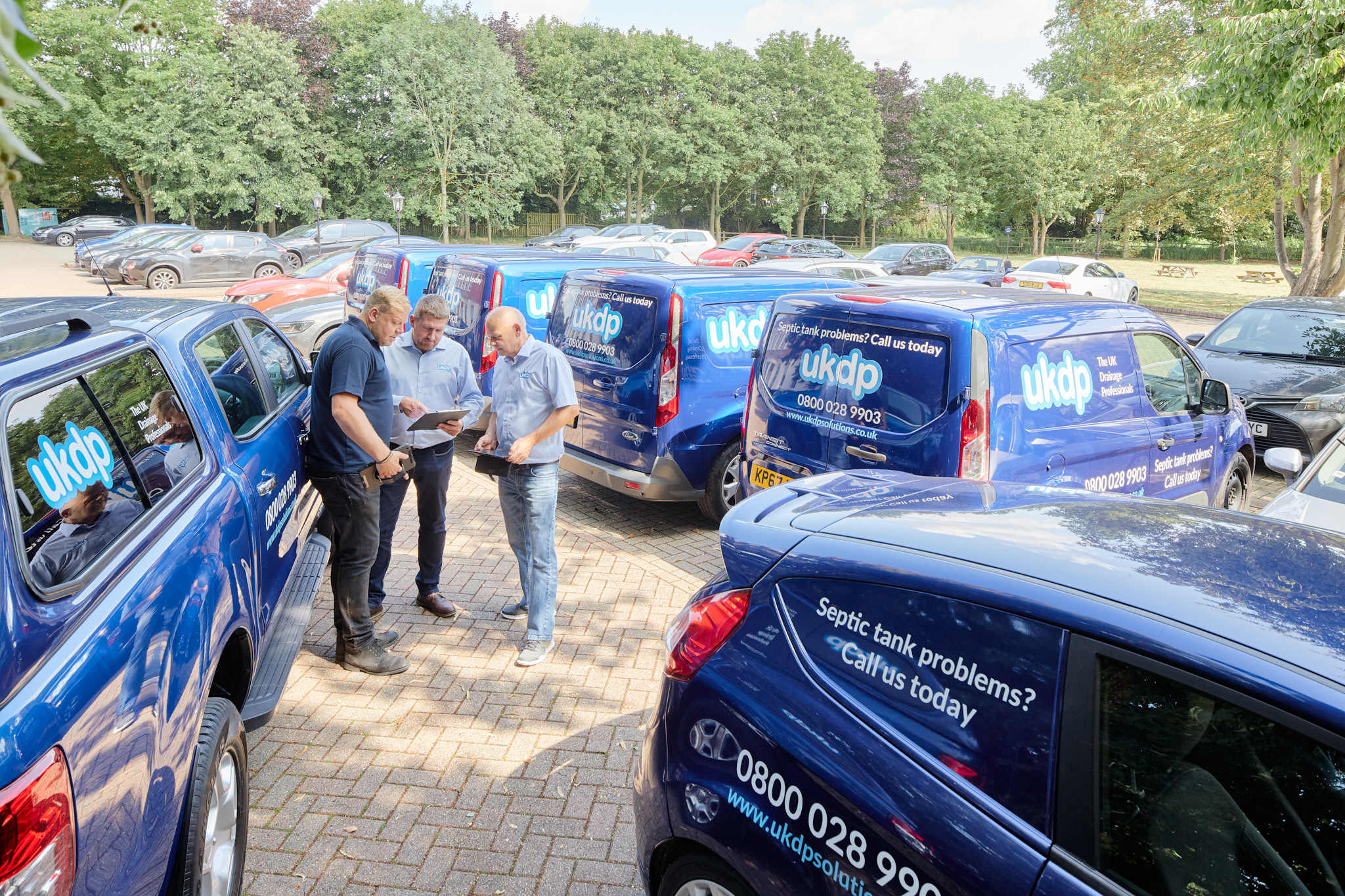 UKDP team with branded vehicle fleet